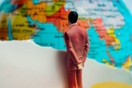 Businessman figure observing a globe model from close-up