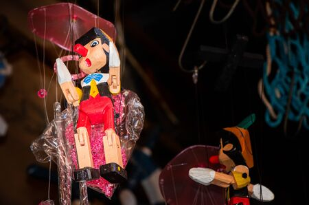 Wooden pinocchio dolls with long nose. Conceptual fairy tale character.