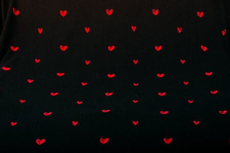 Black fabric background with red hearts shapes