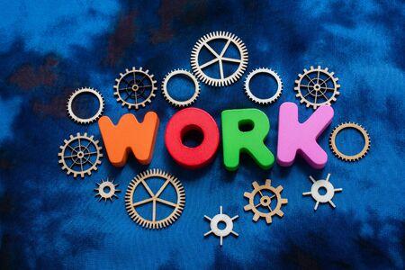Work wording and wooden cogwheels as industry mechanism concept 版權商用圖片