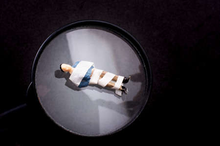 MAn figurine wrapped in bandage on magnifying glass