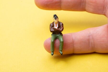 Figurine model men sitting on finger of hand