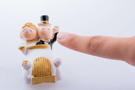 Hand pointing to a newly married husband and wife in a car miniature