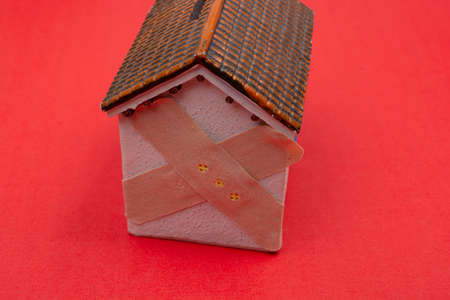 House Model With Crossed Band Aid for medical concept