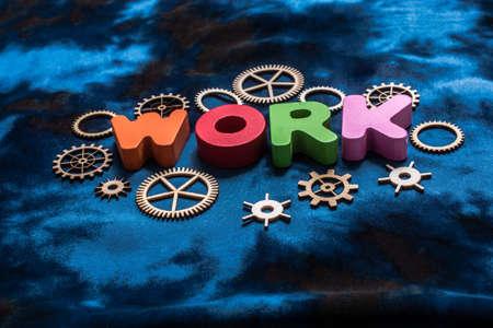 Work wording and wooden cogwheels as industry mechanism concept Stockfoto