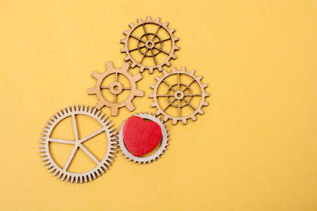 Heart shaped icon and Wooden cogwheels  as love concepts Stockfoto