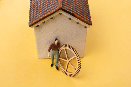 Industrial composition. Man with cogwheel gears by a house