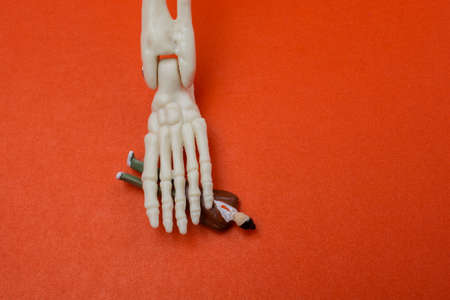 Skeleton hand pressing on man figurine on red . Death concept