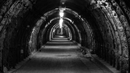 An old, illuminated, hollow underground tunnel in a closed coal mine.