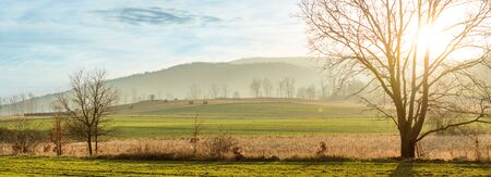 Poland, The setting sun over the mountains and the cultivated field.