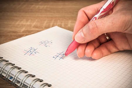 Notebook with a pen prepared for tic-tac-toe. The player enters his value into the notebook. A social game consisting of typing a circle and cross, the one who has three vertically, horizontally or diagonally wins. A way to entertain yourself at home.