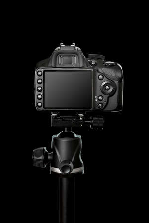 A professional digital camera with a large touch screen, many buttons make the camera easier to use. Camera mounted on a tripod, view from the back on a black background. Imagens