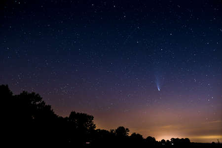 Comet Neowise, an astronomical phenomenon the passage of a comet in front of the constellation Ursa Major. View from the ground to the night sky.