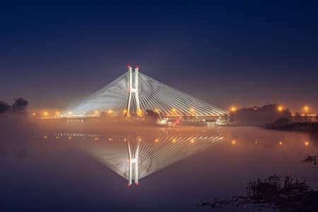 Wroclaw Redzinski Bridge over the Odra River, the illuminated bridge is reflected in the water.