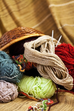 Balls of colored yarn for hand knitting in a decorative basket
