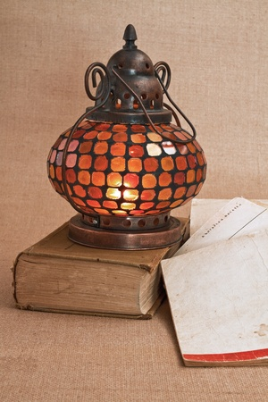 diluted: nterior Oriental brass lamp with a colorful bit of glass and old books about it Stock Photo