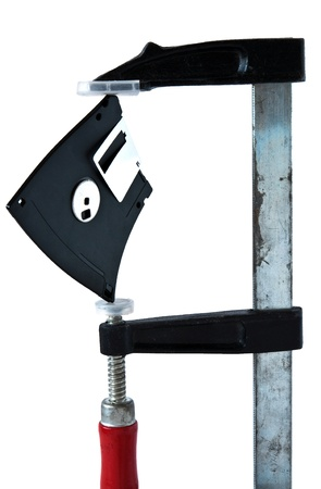 3.5-inch floppy disk between the jaws of the clamp carpenter photo