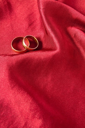 Two wedding rings on red satin background