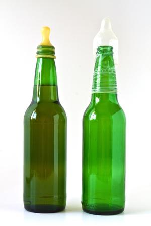 condones: Botella de cerveza completo con un condón de chupete y una botella vacía Foto de archivo