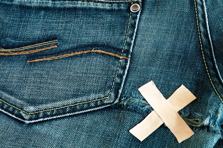 Torn blue jeans with glued cross strapping tape photo