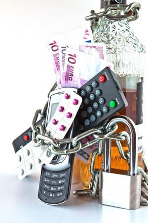 padlocked: Bottle of alcohol, pills, blister, remote TV and cell phone chains with a chain and padlocked Stock Photo