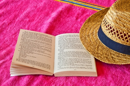 Open book on beach towels and straw hat 版權商用圖片