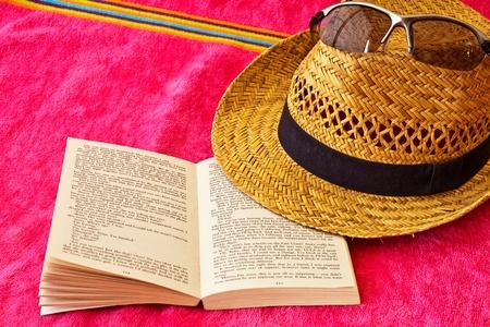 Livre ouvert sur des serviettes de plage et chapeau de paille