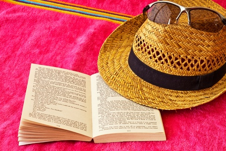 towel: Open book on beach towels and straw hat Stock Photo