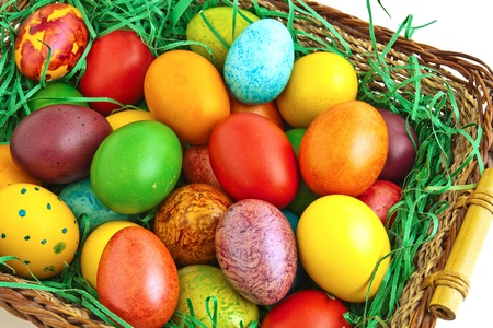 Colorful dyed Easter eggs placed in a wooden basket