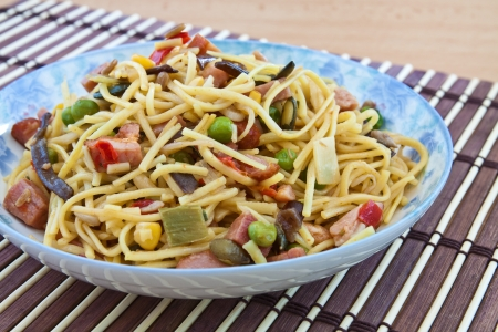Yellow noodles cooked with Chinese vegetable mix and smoked bacon photo