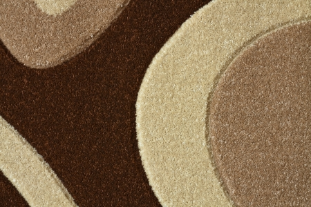 Detail of the carpet in brown, beige and white pastel colors in abstract curves