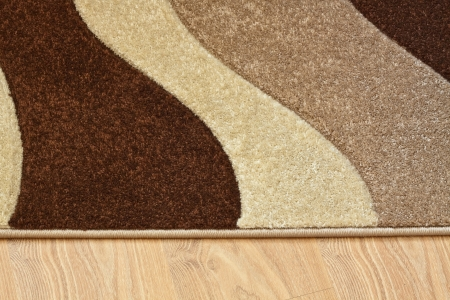 Detail of carpet in brown, beige and white colors on laminate photo