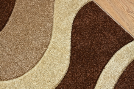 wool rugs: Detail of carpet in brown, beige and white colors on laminate