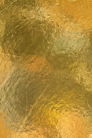 Sheet of gold foil with surface scratches and dark spots photo