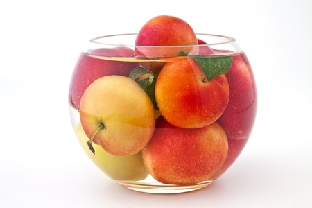 Fresh and juicy plums in a glass of water on white background photo