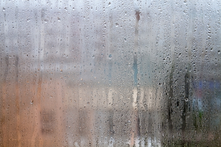 vertically: Misted glass windows streaming vertically small water drops