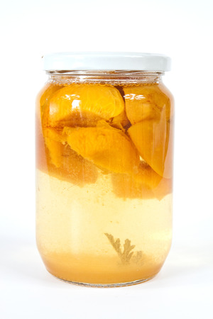 Compote made ??of chopped fresh fruit with sugar syrup enclosed in glass jar photo