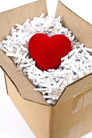 Red plush heart in an open cardboard box with shredded paper around it photo