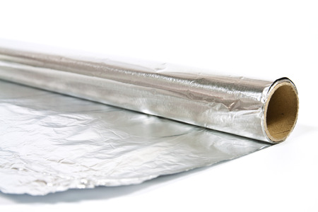 Roll of household aluminum foil on white background photo