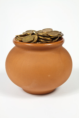 Clay pot with gold coins on a white background photo