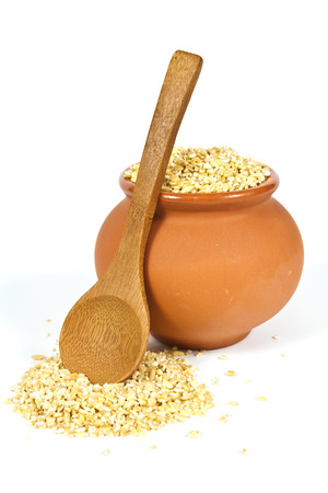 kasha: Manna croup in a clay pot with a wooden spoon on a white background