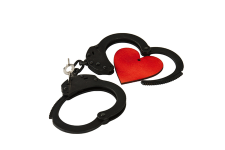 Black oxide handcuffs and red wooden heart on a white background