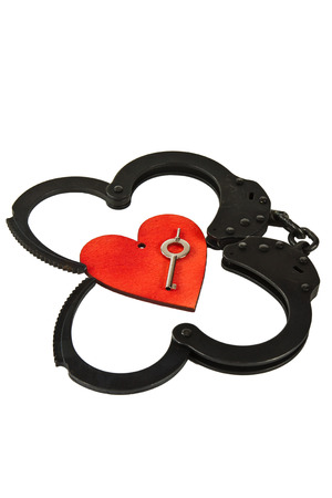 oxide: Black oxide handcuffs and red wooden heart on a white background