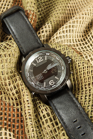 cronógrafo: Reloj cronógrafo de los hombres en redes de camuflaje Foto de archivo