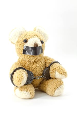 Plush teddy bear with handcuffs on white background