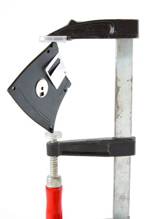 Diskette caught in carpentry clamps on a white background