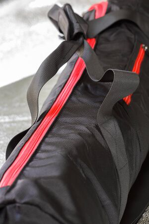 Black photographic tripod case with spectacular red zipper.Selective focus with shallow depth of field.