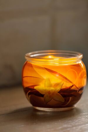 Vanilla candle lit in a glass jar.Selective focus with shallow depth of field.