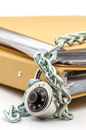 Cardboard document folders locked with chain and padlock. Selective focus with shallow depth of field.