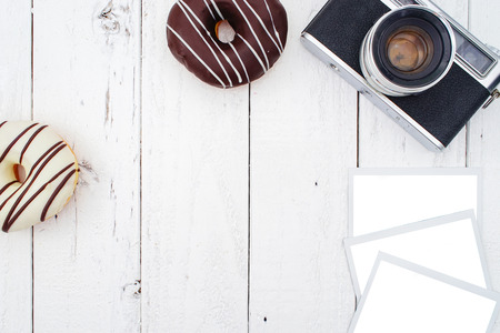 donut style: Vintage Camera, Instax Photos and Donut on White Wooden Background, Flat Lay Style with Free Text Space Stock Photo